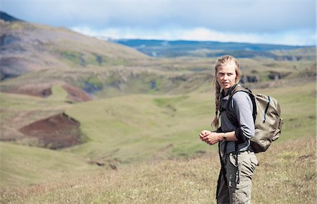 Hiker wearing backpack on hillside Stock Photo - Premium Royalty-Free, Code: 649-06305445