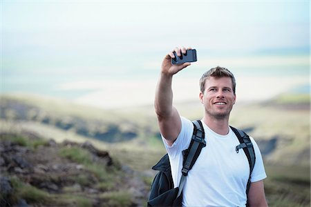 Hiker taking picture with cell phone Stock Photo - Premium Royalty-Free, Code: 649-06305446