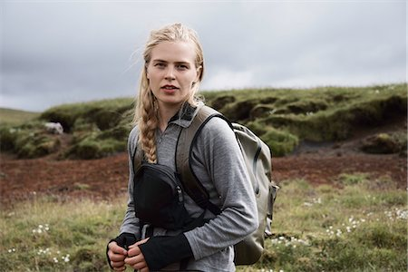 Hiker carrying backpack on hillside Stock Photo - Premium Royalty-Free, Code: 649-06305454
