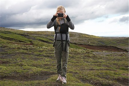 Hiker taking pictures on hillside Stock Photo - Premium Royalty-Free, Code: 649-06305455