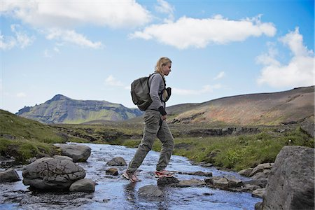 Hiker crossing rocky rural stream Stock Photo - Premium Royalty-Free, Code: 649-06305450