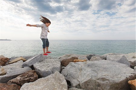 Girl playing on rocks at beach Stock Photo - Premium Royalty-Free, Code: 649-06305490