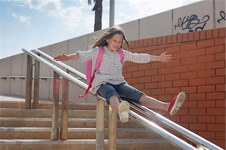 Girl sliding down banister on steps Stock Photo - Premium Royalty-Free, Code: 649-06305500