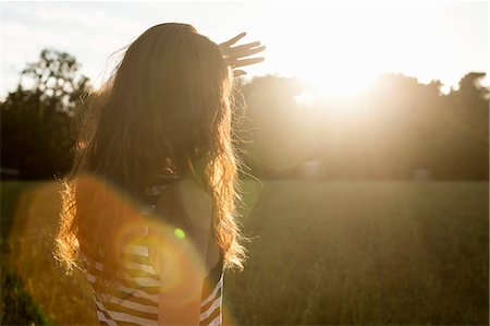 Woman shielding her eyes from sun Stock Photo - Premium Royalty-Free, Code: 649-06305544