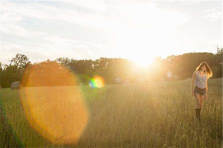 Smiling woman walking in grassy field Stock Photo - Premium Royalty-Free, Code: 649-06305549