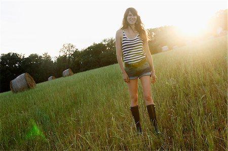 Smiling woman walking in grassy field Stock Photo - Premium Royalty-Free, Code: 649-06305550
