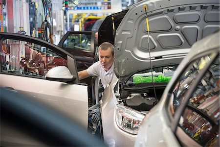 Worker fitting doors in car in car factory Stock Photo - Premium Royalty-Free, Code: 649-06305645