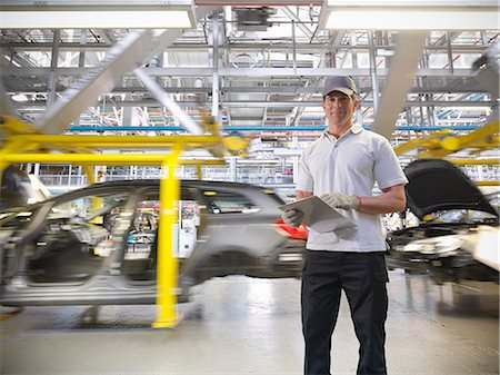Portrait of worker with cars on production line in car factory Stock Photo - Premium Royalty-Free, Code: 649-06305642