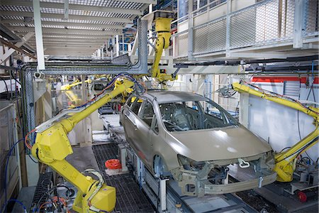 stamped - Robots applying sealant to cars in car factory Stock Photo - Premium Royalty-Free, Code: 649-06305666