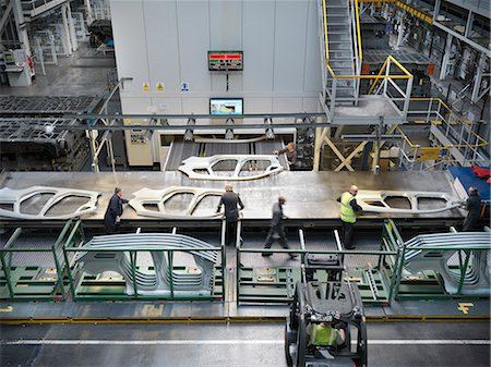 High angle view of workers handling car parts as they come out of press in car factory Stock Photo - Premium Royalty-Free, Code: 649-06305680