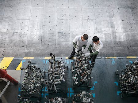 production - High angle view of engineers inspecting press parts in car factory Stock Photo - Premium Royalty-Free, Code: 649-06305682
