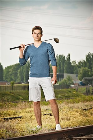 Man playing golf on train tracks Stock Photo - Premium Royalty-Free, Code: 649-06305710