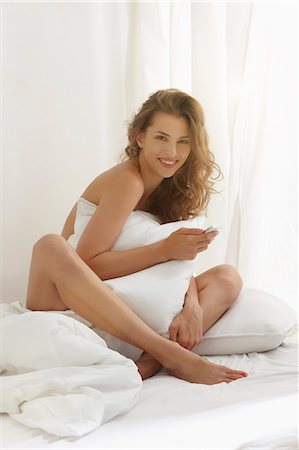 Nude woman covering body with pillow Stock Photo - Premium Royalty-Free, Code: 649-06305745
