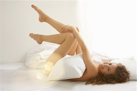 Nude woman covering body with pillow Stock Photo - Premium Royalty-Free, Code: 649-06305749
