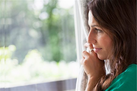 Smiling woman peering out window Stock Photo - Premium Royalty-Free, Code: 649-06305779