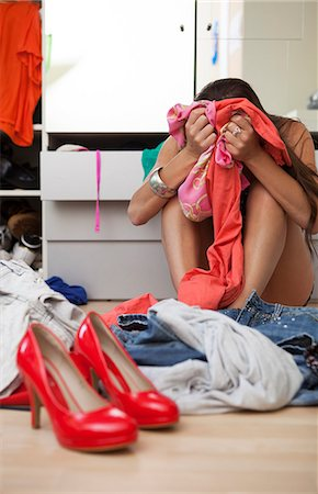 Woman clutching her clothes in bedroom Stock Photo - Premium Royalty-Free, Code: 649-06305773