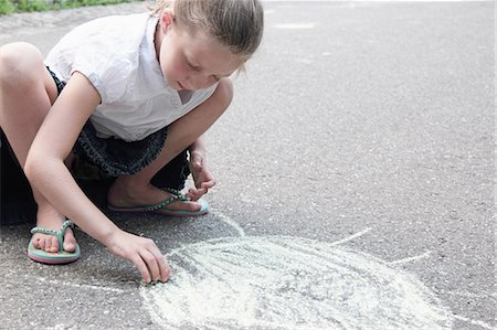Girl drawing sun on sidewalk in chalk Stock Photo - Premium Royalty-Free, Code: 649-06305826