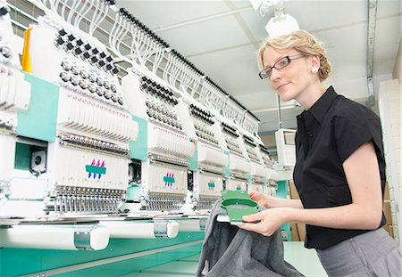 Worker examining fabric in factory Stock Photo - Premium Royalty-Free, Code: 649-06305905