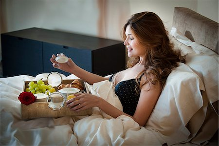 Woman eating breakfast in bed Stock Photo - Premium Royalty-Free, Code: 649-06305914