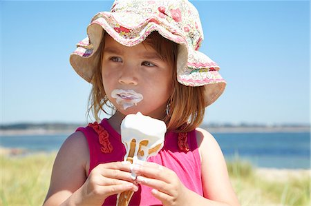 Girl eating ice cream on beach Stock Photo - Premium Royalty-Free, Code: 649-06352474