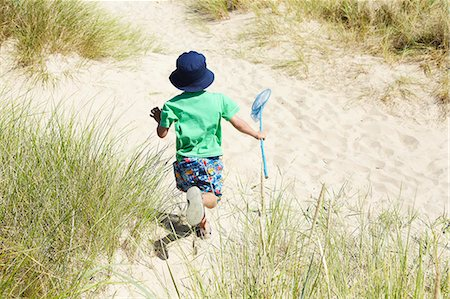 Boy carrying fishing net on beach Stock Photo - Premium Royalty-Free, Code: 649-06352471