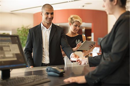 person on phone with credit card - Businessman checking into hotel Stock Photo - Premium Royalty-Free, Code: 649-06352483