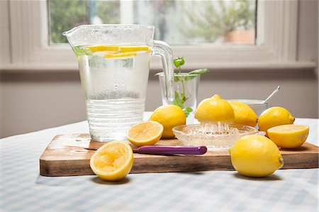 Lemons, juicer and pitcher of water Stock Photo - Premium Royalty-Free, Code: 649-06352609
