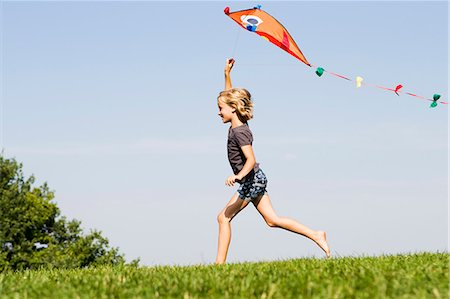 Girl playing with kite outdoors Stock Photo - Premium Royalty-Free, Code: 649-06352634