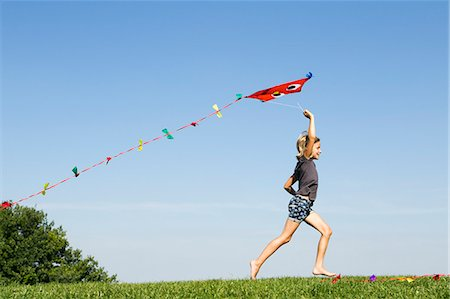 Girl playing with kite outdoors Stock Photo - Premium Royalty-Free, Code: 649-06352630