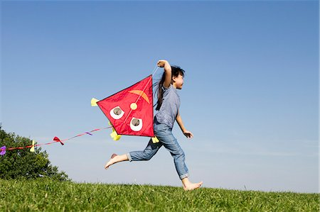 Girl playing with kite outdoors Stock Photo - Premium Royalty-Free, Code: 649-06352633
