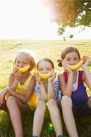 Girls holding bananas over mouths Stock Photo - Premium Royalty-Free, Code: 649-06352647
