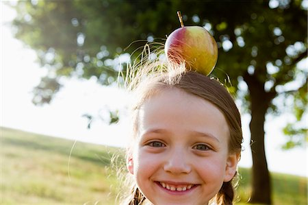 Smiling girl balancing apple on head Stock Photo - Premium Royalty-Free, Code: 649-06352656