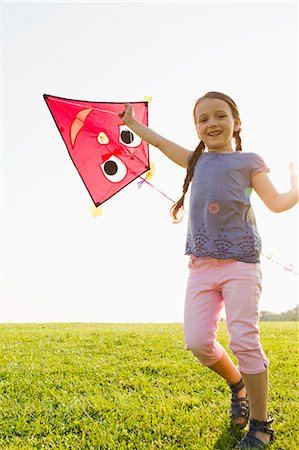Girl playing with kite outdoors Stock Photo - Premium Royalty-Free, Code: 649-06352658
