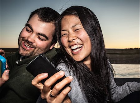 showing - Couple using cell phones outdoors Stock Photo - Premium Royalty-Free, Code: 649-06352753