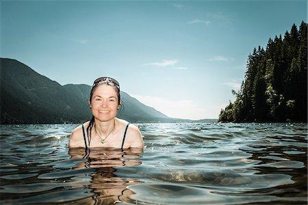 Woman standing in still lake Stock Photo - Premium Royalty-Free, Code: 649-06352774