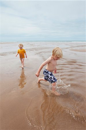 Children playing in waves on beach Stock Photo - Premium Royalty-Free, Code: 649-06352912