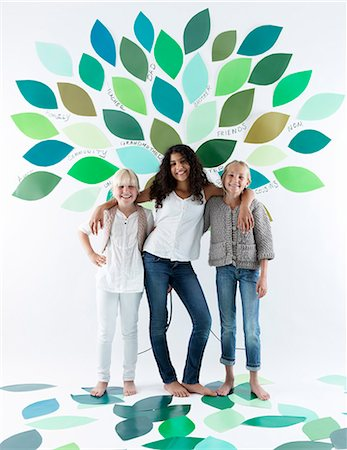 Girls standing under tree on wall Stock Photo - Premium Royalty-Free, Code: 649-06352958