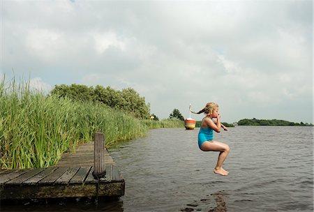 Girl jumping into rural lake Stock Photo - Premium Royalty-Free, Code: 649-06352994
