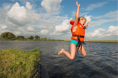 Girl jumping into rural lake Stock Photo - Premium Royalty-Free, Code: 649-06352998