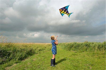 Girl flying kite in rural field Stock Photo - Premium Royalty-Free, Code: 649-06353000