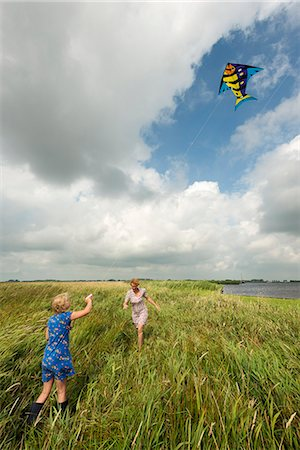 flying happy woman images - Mother and daughter flying kite in field Stock Photo - Premium Royalty-Free, Code: 649-06353001
