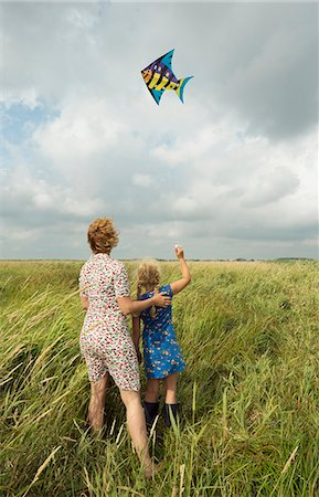 Mother and daughter flying kite in field Stock Photo - Premium Royalty-Free, Code: 649-06353002