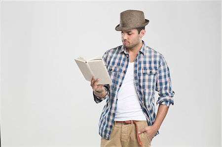 Man reading book with hand in pocket Stock Photo - Premium Royalty-Free, Code: 649-06353176