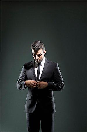 Businessman buttoning suit jacket Stock Photo - Premium Royalty-Free, Code: 649-06353196