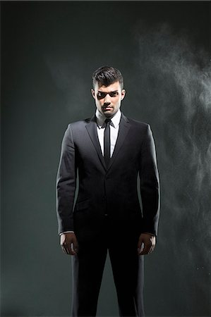 Businessman standing in smoky room Stock Photo - Premium Royalty-Free, Code: 649-06353197