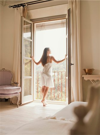 Woman walking on to balcony Stock Photo - Premium Royalty-Free, Code: 649-06353217
