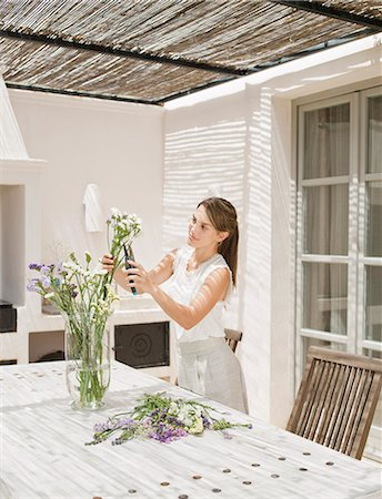 Woman arranging flowers in kitchen Stock Photo - Premium Royalty-Free, Code: 649-06353212