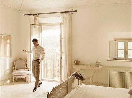 rich lifestyle - Businessman having wine in bedroom Stock Photo - Premium Royalty-Free, Code: 649-06353248
