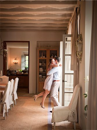 rich lifestyle - Couple hugging in dining room Stock Photo - Premium Royalty-Free, Code: 649-06353258