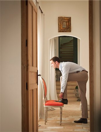 rich lifestyle - Businessman tying his shoe in home Stock Photo - Premium Royalty-Free, Code: 649-06353260